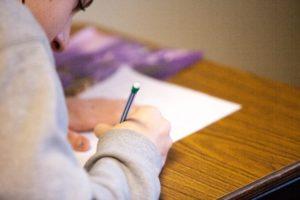 garçon vu de dos écrit sur une feuille