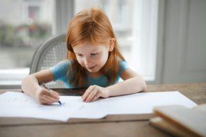 une fillette écrit en souriant
